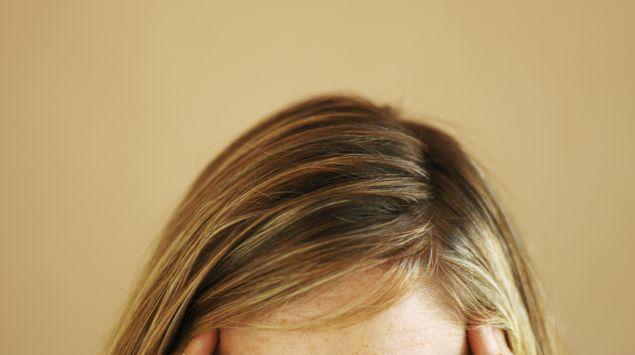 Das Bild zeigt eine blonde Frau, die ihre Hände an die Schläfen hält.