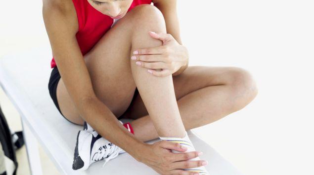 Das Bild zeigt eine Frau in Sportkleidung auf einer Liege sitzend. Ein Fuß ist mit einem Turnschuh bekleidet, der zweite ist bandagiert und sie hält ihn.