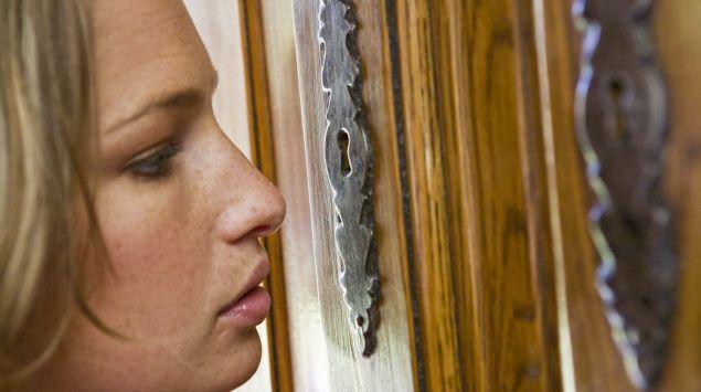 Das Bild zeigt eine Frau, die durch ein Schlüsselloch sieht.
