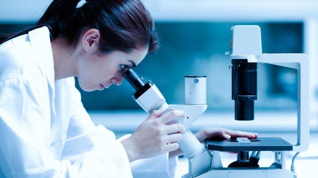 Das Bild zeigt eine Frau, die durch ein Mikroskop schaut.