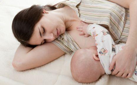 Eine Mutter stillt ihr Kind im Liegen.