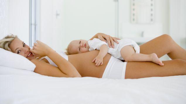 Das Bild zeigt eine Frau und ein Baby im Bett.
