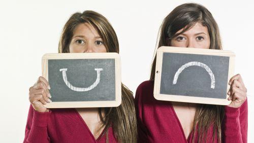 Zwei Frauen, eine mit einem lachenden, eine mit einem traurigen Smiley auf einem Schild.