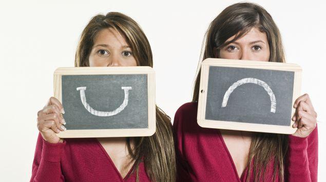Eine Frau hält einen traurigen und einen lustigen Smiley vors Gesicht: Extreme Stimmungsschwankungen können auf eine Erkrankung hinweisen.