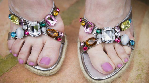 Das Bild zeigt offene Schuhe mit Schmucksteinen.