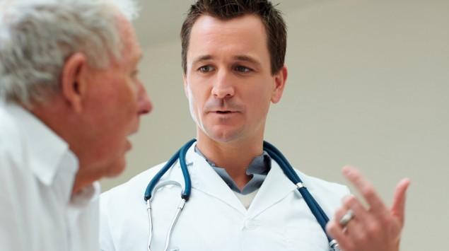 Das Bild zeigt ein Gespräch zwischen einem älteren Patienten und einem Arzt.