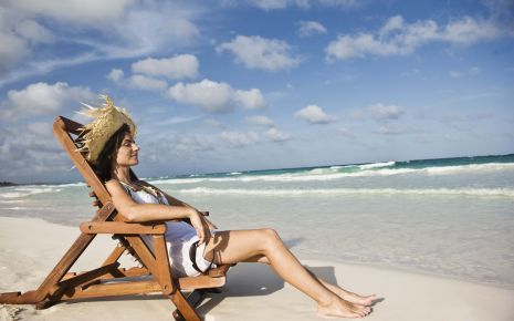Eine Frau sonnt sich in einem Liegestuhl am Strand.
