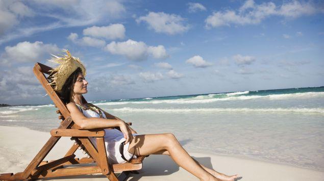 Eine sonnt sich in einem Liegestuhl am Strand.