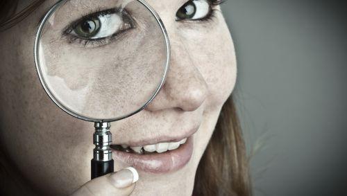 Das Bild zeigt eine junge Frau mit einer Lupe vor dem Auge.