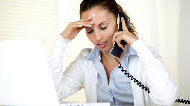 Das Bild zeigt eine junge Frau mit Kopfschmerzen, die am Laptop sitzt und telefoniert.