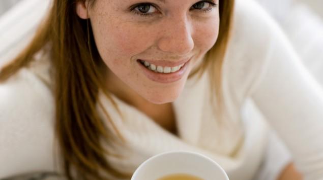 Eine Frau hält eine Tasse Tee in der Hand.