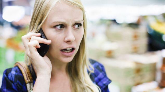 Eine ängstlich wirkende Frau telefoniert mit dem Handy.