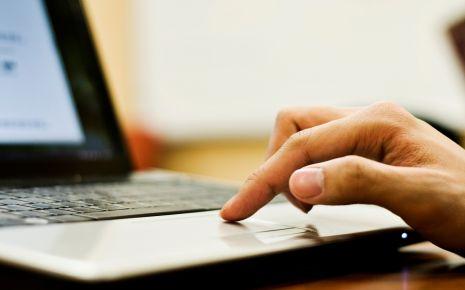 Man sieht einen Finger auf dem Touchpad eines Laptops.