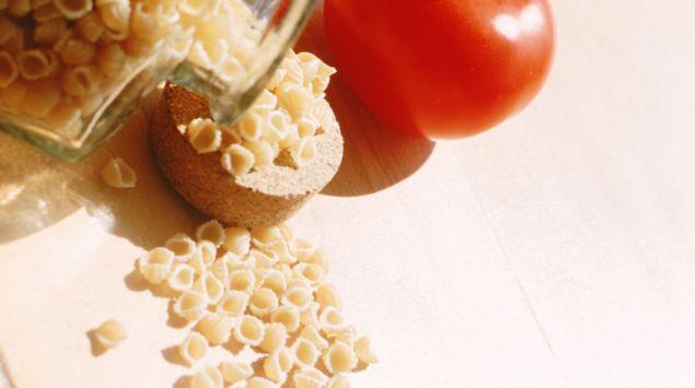 Das Bild zeigt eine Flasche mit Nudeln und eine Tomate.