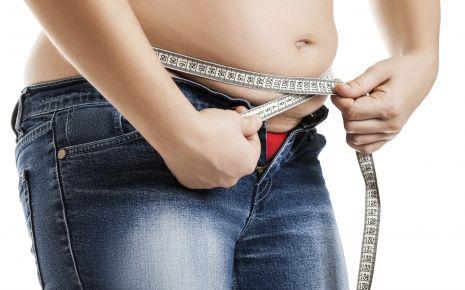 Eine Frau misst den Umfang ihres Bauches.