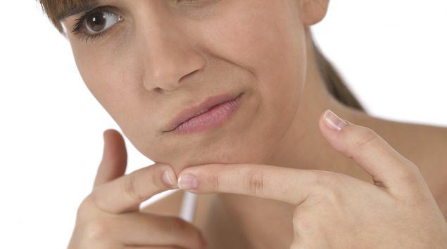 Eine junge Frau drückt einen Pickel am Kinn aus.
