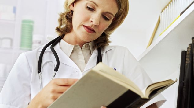 Das Bild zeigt eine Ärztin, die in einem Buch liest.