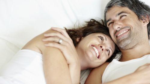 Das Bild zeigt ein lächelndes Paar auf einem Bett liegend.