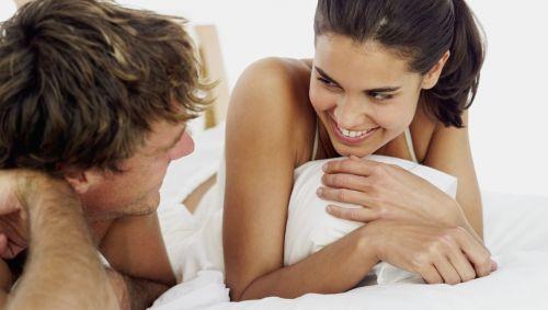 Eine Frau und ein Mann liegen im Bett und lächeln sich an.