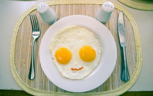 Das Bild zeigt einen Teller mit einem Spiegelei, das wie ein Kopf aussieht, sowie Messer, Gabel, Pfeffer und Salz.