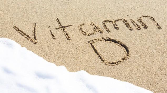 Das Bild zeigt die Worte Vitamin D in den Sand geschrieben.