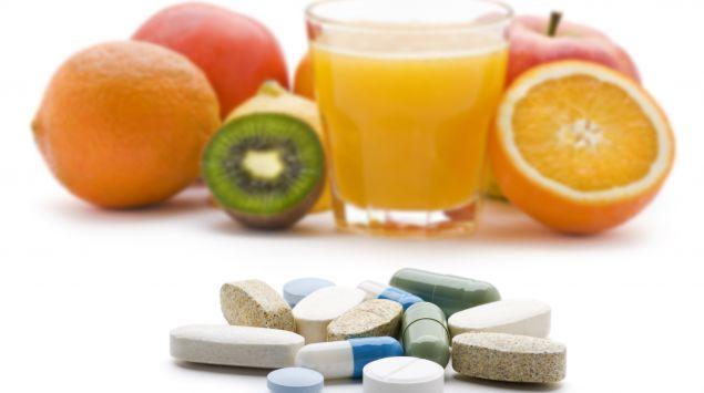 Man im Hintergrund Obst und ein Glas Orangensaft, im Vordergrund liegen verschiedene Tabletten.