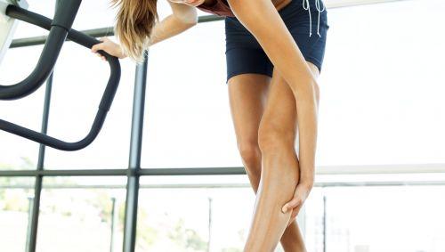 Das Bild zeigt eine Frau, die sich an ihr Bein fasst.
