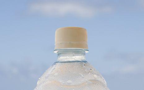 Eine Wasserflasche, im Hintergrund das Meer.