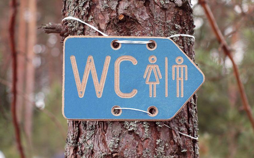 Ein WC-Schild hängt an einem Baum.