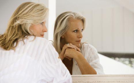 Das Bild zeigt eine ältere Frau, die vor einem Spiegel sitzt.
