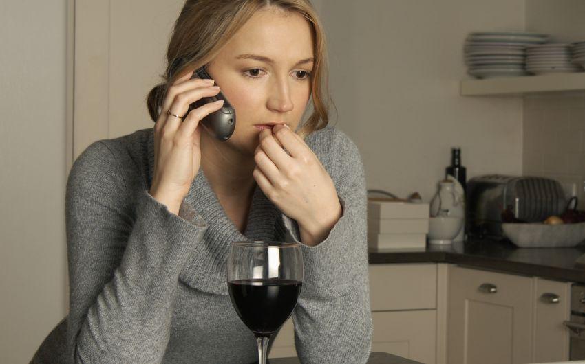 Eine Frau sitzt telefonierend am Küchentisch und hat vor sich ein Glas Wein.