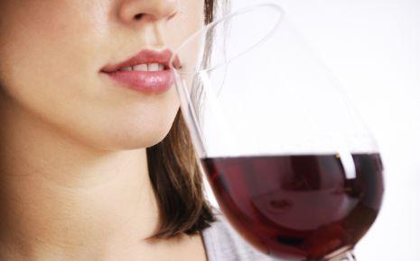 Das Bild zeigt eine Frau, die ein Glas Wein trinkt.