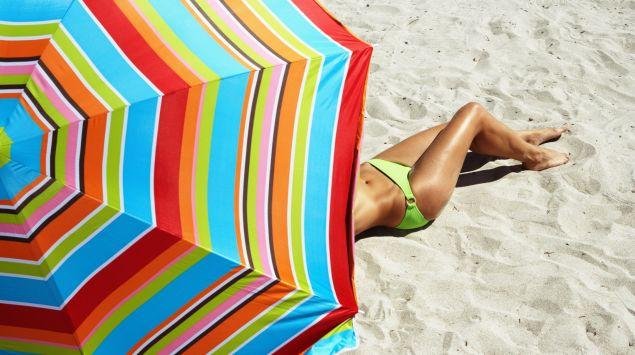 Das Bild zeigt einen Sonnenschirm und eine Frau, die sich sonnt.