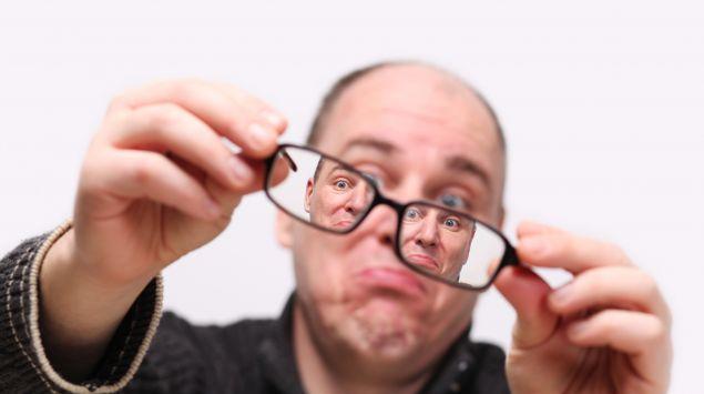 Das Bild zeigt einen Mann durch eine Brille betrachtet.