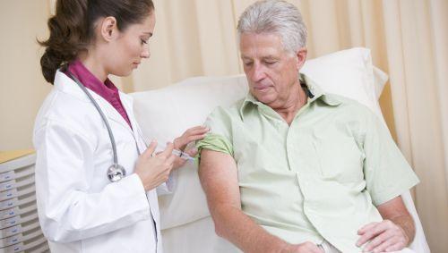 Das Bild zeigt einen Patienten, der eine Spritze bekommt.