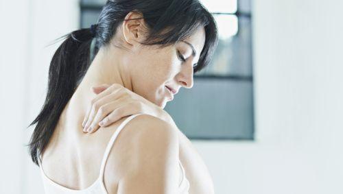 Das Bild zeigt eine Frau, die sich in den Nacken greift.