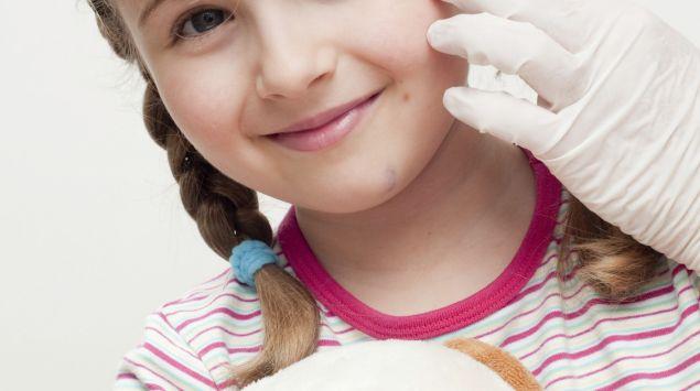 Das Bild zeigt ein Kind, welches ein Pflaster auf die Stirn bekommt.