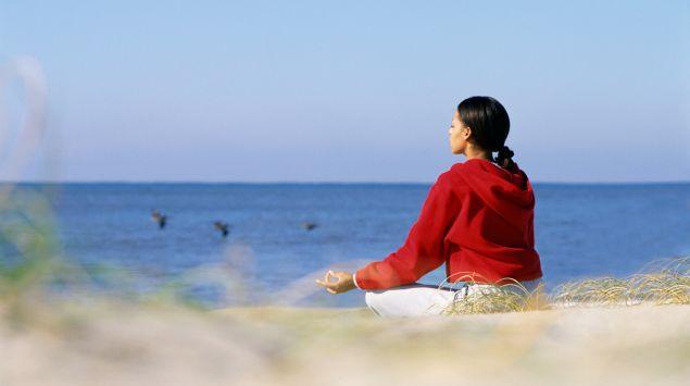 Das Bild zeigt eine Frau im Schneidersitz am Meer.