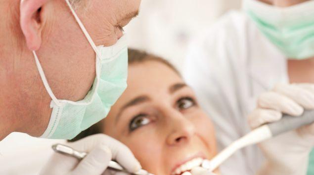 Das Bild zeigt einen Zahnarzt, der eine Frau untersucht.