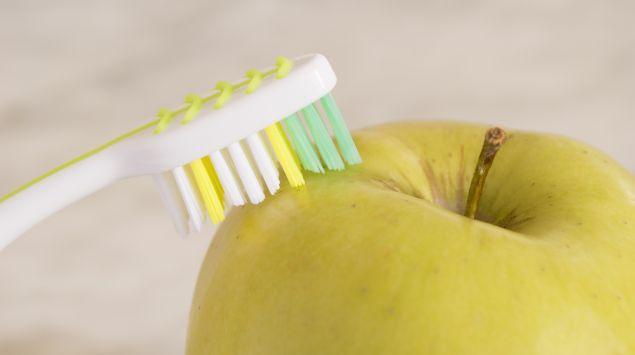 Das Bild zeigt eine Zahnbürste und einen Apfel.