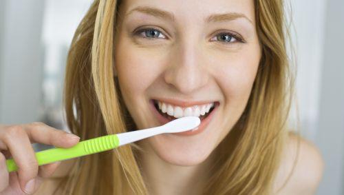 Man sieht eine Frau, die sich die Zähne putzt.