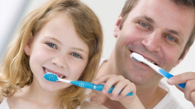 Das Bild zeigt ein Mädchen und einen Mann beim Zähneputzen.