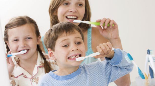 Das Bild zeigt eine Frau, einen Jungen und ein Mädchen beim Zähneputzen.