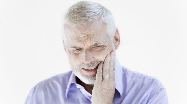 Ein Mann hält sich vor Schmerz die Hand an eine Wange.
