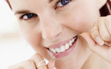 Eine Frau benutzt Zahnseide.