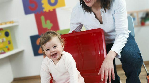 Das Bild zeigt eine Frau, die mit einem Kleinkind spielt.