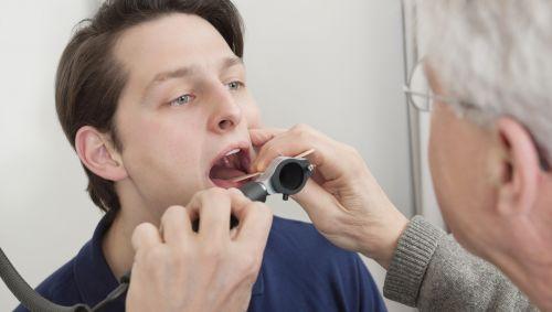 Ein Arzt schaut einem jungen Mann in den Mund.