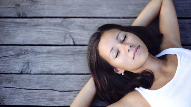 Das Bild zeigt eine Frau, die mit dem Rücken auf einem Holzboden liegt.