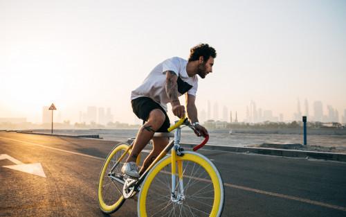 Ein junger Mann fährt auf einem gelben Rennrad.