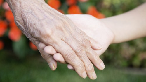 Auf dem Bild wird die Hand einer älteren Frau gehalten.